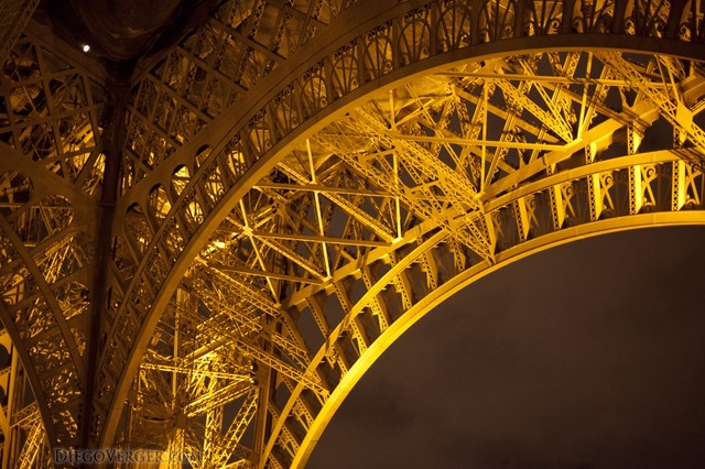 Detail of the arch of the Eiffel Tower at night - Paris, France