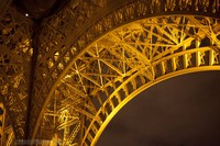 Detail of the arch of the Eiffel Tower at night - Thumbnail