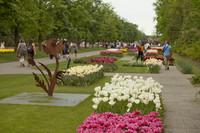 Una escultura y macizos de flores en los caminos de Keukenhof - Lisle, Países Bajos