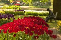 Tulipanes rojos junto a la escultura del hombre sentado de Keukenhof - Lisse, Países Bajos